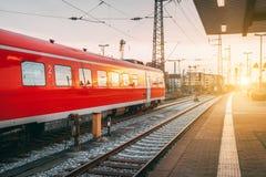 Όμορφος σιδηροδρομικός σταθμός με τη σύγχρονη κόκκινη αμαξοστοιχία περιφερειακού σιδηροδρόμου στο ηλιοβασίλεμα Στοκ Φωτογραφία
