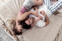 Όμορφος σκοτεινός-μαλλιαρός νεαρός άνδρας σε ένα άσπρο πουκάμισο και η χαριτωμένη ξανθή σύζυγός του που μένει στο κρεβάτι στοκ εικόνα με δικαίωμα ελεύθερης χρήσης