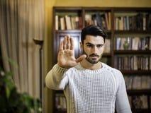 Όμορφος, σοβαρός νεαρός άνδρας που κάνει το σημάδι στάσεων με το χέρι Στοκ Φωτογραφίες