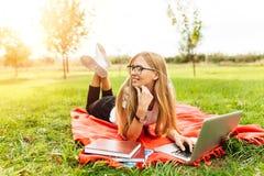 Όμορφος σπουδαστής κοριτσιών με τα γυαλιά που εργάζεται σε ένα lap-top σε ένα γ στοκ εικόνες με δικαίωμα ελεύθερης χρήσης