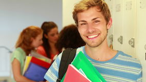Όμορφος σπουδαστής που κλίνει στο ντουλάπι που χαμογελά στη κάμερα απόθεμα βίντεο