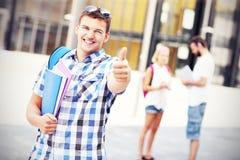 Όμορφος σπουδαστής που παρουσιάζει εντάξει σημάδι στην πανεπιστημιούπολη Στοκ εικόνα με δικαίωμα ελεύθερης χρήσης
