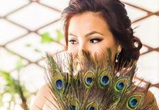 Όμορφος στενός επάνω γυναικών με τον ανεμιστήρα φιαγμένο από φτερό peacock Στοκ Εικόνες