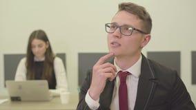 Όμορφος στοχαστικός νεαρός άνδρας πορτρέτου στα γυαλιά που κάθεται στο πρώτο πλάνο στο γραφείο ενώ η γυναίκα συνάδελφός του μέσα απόθεμα βίντεο