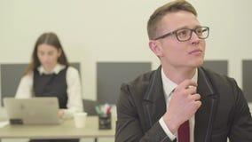 Όμορφος στοχαστικός νεαρός άνδρας πορτρέτου στα γυαλιά που κάθεται στο πρώτο πλάνο στο γραφείο ενώ η γυναίκα συνάδελφός του μέσα φιλμ μικρού μήκους