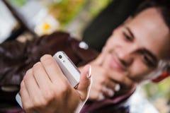 Όμορφος στοχαστικός νεαρός άνδρας που κρατά το έξυπνο τηλέφωνο και που εξετάζει το καθμένος στον καφέ υπαίθρια Εκλεκτική εστίαση Στοκ φωτογραφίες με δικαίωμα ελεύθερης χρήσης
