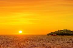 Όμορφος στρογγυλός και φωτεινός ήλιος που θέτει ενάντια σε ένα ζωηρό πορτοκαλί SK Στοκ εικόνες με δικαίωμα ελεύθερης χρήσης