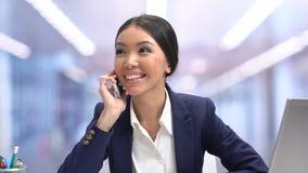 Όμορφος συναισθηματικός εργαζόμενος γραφείων θηλυκών που κουβεντιάζει στο τηλέφωνο στο σπάσιμο, χαλάρωση απόθεμα βίντεο