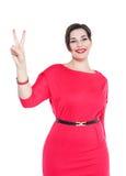 Όμορφος συν τη γυναίκα μεγέθους στο κόκκινο φόρεμα με τη νίκη που απομονώνεται Στοκ Εικόνα