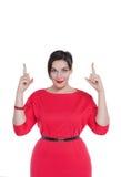 Όμορφος συν τη γυναίκα μεγέθους στο κόκκινο φόρεμα που παρουσιάζει σε κάτι από το φ Στοκ Φωτογραφίες