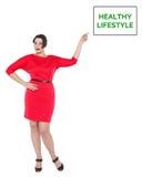 Όμορφος συν τη γυναίκα μεγέθους στο κόκκινο φόρεμα που παρουσιάζει υγιή σε πιό lifest Στοκ φωτογραφία με δικαίωμα ελεύθερης χρήσης