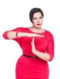 Όμορφος συν τη γυναίκα μεγέθους στο κόκκινο φόρεμα που παρουσιάζει χρονική έξω χειρονομία Στοκ Εικόνες