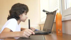 Όμορφος σύγχρονος έφηβος αγοριών που εργάζεται σε μια γραφική ταμπλέτα εξετάζει την οθόνη lap-top r απόθεμα βίντεο