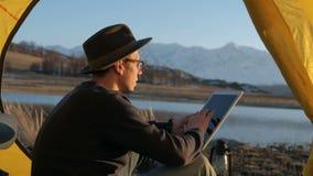 Όμορφος τουρίστας νεαρών άνδρων που χρησιμοποιούν το τηλέφωνο κυττάρων και φορητός μίνι ομιλητής στην τουριστική δεκαετία του '20 φιλμ μικρού μήκους