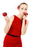 Όμορφος το κορίτσι στο κόκκινο φόρεμα που κρατά την κόκκινη Apple Στοκ Φωτογραφίες