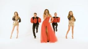 Όμορφος τραγουδιστής σε ένα κόκκινο φόρεμα, που τραγουδά και που χορεύει στο στούντιο σε ένα άσπρο υπόβαθρο απόθεμα βίντεο
