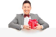 Όμορφος τύπος με το δεσμό τόξων που κρατά ένα δώρο πίσω από μια επιτροπή Στοκ φωτογραφία με δικαίωμα ελεύθερης χρήσης