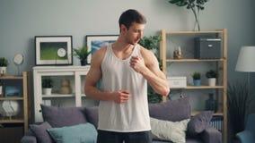 Όμορφος τύπος που εξετάζει το χαμόγελο καμερών που μιλά παρουσιάζοντας μυς που στέκονται στο σπίτι απόθεμα βίντεο