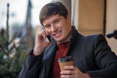 Όμορφος τύπος που μιλά στο τηλέφωνο κυττάρων χαμογελώντας Στοκ φωτογραφία με δικαίωμα ελεύθερης χρήσης