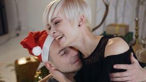 Όμορφος τύπος στη ερωτευμένη αγκαλιάζοντας φίλη καπέλων Άγιου Βασίλη στη νύχτα Χριστουγέννων ή το νέο έτος ευτυχείς νεολαίες αγάπ απόθεμα βίντεο