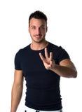 Όμορφος υπολογισμός νεαρών άνδρων σε τρία με τα δάχτυλα και τα χέρια στοκ φωτογραφία με δικαίωμα ελεύθερης χρήσης