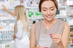 Όμορφος φαρμακοποιός κοριτσιών που βοηθά έναν πελάτη στοκ φωτογραφίες