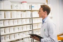 Όμορφος φαρμακοποιός που εξετάζει την ιατρική στοκ εικόνα