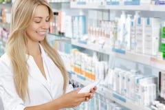 Όμορφος φαρμακοποιός που επιλέγει το προϊόν στοκ φωτογραφία με δικαίωμα ελεύθερης χρήσης