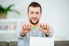 Όμορφος χαμογελώντας νεαρός άνδρας που παρουσιάζει στο σπίτι usb κλειδί στοκ εικόνες με δικαίωμα ελεύθερης χρήσης