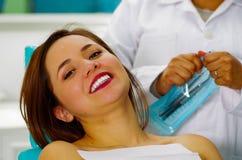 Όμορφος χαμογελώντας ασθενής γυναικών που έχει την οδοντική θεραπεία στο γραφείο οδοντιάτρων ` s, με έναν γιατρό πίσω από την εκμ Στοκ εικόνα με δικαίωμα ελεύθερης χρήσης