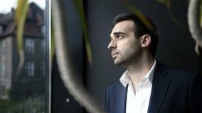 Όμορφος χαμογελώντας βέβαιος επιχειρηματίας που εξετάζει το παράθυρο απόθεμα βίντεο