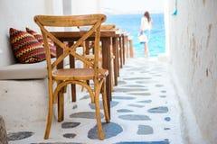 Όμορφος χαρακτηριστικός ελληνικός υπαίθριος καφές στη Μύκονο με την καταπληκτική άποψη θάλασσας σχετικά με τα νησιά των Κυκλάδων στοκ εικόνα
