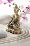 Όμορφος χαλκός Βούδας στα λουλούδια χαλικιών άμμου Στοκ Φωτογραφία