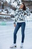 Όμορφος χειμώνας πατινάζ πάγου γυναικών υπαίθρια, χαμόγελο του προσώπου Βουνά στην ανασκόπηση στοκ φωτογραφία με δικαίωμα ελεύθερης χρήσης