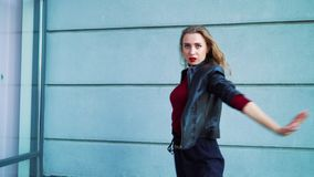 Όμορφος χορευτής γυναικών που αποδίδει ενάντια στον γκρίζο κατασκευασμένο τοίχο υπαίθρια απόθεμα βίντεο