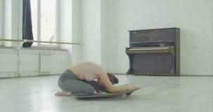 Όμορφος χορευτής μπαλέτου που τεντώνει έξω τους μυς φιλμ μικρού μήκους