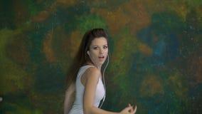 Όμορφος χορός νέων κοριτσιών Ακούει τη μουσική στα ακουστικά Πολύ συμπαθητικές κινήσεις απόθεμα βίντεο