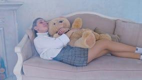 Όμορφος ύπνος κοριτσιών στον καναπέ σε έναν εναγκαλισμό με μια teddy αρκούδα απόθεμα βίντεο