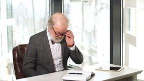 Όμορφος ώριμος επιχειρηματίας στο κλασικό κοστούμι και eyeglasses που λειτουργούν στο γραφείο του φιλμ μικρού μήκους