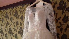 Όμορφο άσπρο γαμήλιο φόρεμα για τη νύφη στο εσωτερικό Θηλυκά ενδύματα δαντελλών για τον εορτασμό απόθεμα βίντεο