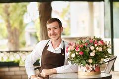 Όμορφο άτομο ανθοκόμων με τα φρέσκα λουλούδια σε ένα υπόβαθρο καταστημάτων Επιχειρησιακή έννοια ανθοκόμων διάστημα αντιγράφων Στοκ Εικόνες