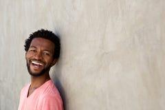 Όμορφο άτομο αφροαμερικάνων που κλίνει ενάντια στον τοίχο και το γέλιο Στοκ Εικόνες