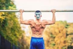 Όμορφο άτομο γυμνοστήθων που κάνει το πηγούνι UPS στο πάρκο, που φορά μια μάσκα anonymus Φορέας ικανότητας, προσωπικός εκπαιδευτή Στοκ εικόνες με δικαίωμα ελεύθερης χρήσης