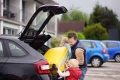 Όμορφο άτομο και ο μικρός γιος του που πηγαίνουν στις διακοπές, που φορτώνουν τη βαλίτσα τους στον κορμό αυτοκινήτων Στοκ εικόνα με δικαίωμα ελεύθερης χρήσης