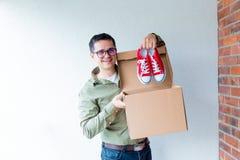 Όμορφο άτομο με την κίνηση των κιβωτίων και των κόκκινων gumshoes Στοκ Φωτογραφία