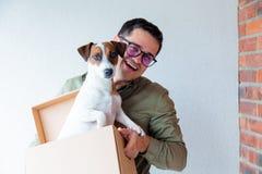 Όμορφο άτομο με την κίνηση των κιβωτίων και του σκυλιού στο άσπρο υπόβαθρο Στοκ εικόνα με δικαίωμα ελεύθερης χρήσης