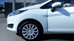 Όμορφο άτομο με την μπλε μπροστινή πόρτα αυτοκινήτων περίπτωσης ανοίγοντας που ξεπερνά το άσπρο σύγχρονο ολοκαίνουργιο αυτοκινητι φιλμ μικρού μήκους