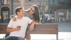 Όμορφο άτομο με τη διαθέσιμη συνεδρίαση χεριών φλιτζανιών του καφέ στον πάγκο στο τετράγωνο πόλεων Ελκυστική γυναίκα που αγκαλιάζ απόθεμα βίντεο