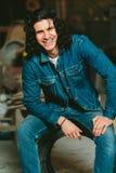 Όμορφο άτομο με το μακρυμάλλες brunette σε ένα σακάκι τζιν Στοκ Εικόνες
