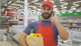 Όμορφο άτομο παράδοσης στην κόκκινη ομοιόμορφη ομιλία στην τσάντα εγγράφου κινητών και παντοπωλείων κρατήματος με τα λαχανικά απόθεμα βίντεο